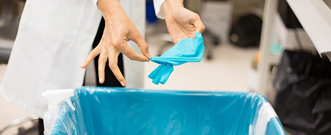 """A doctor removing a disposable glove, illustrating a section titled, """"What is Infection Control?"""""""