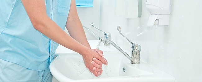 A healthcare professional washing their hands as part of a set infection control protocol in a healthcare setting.